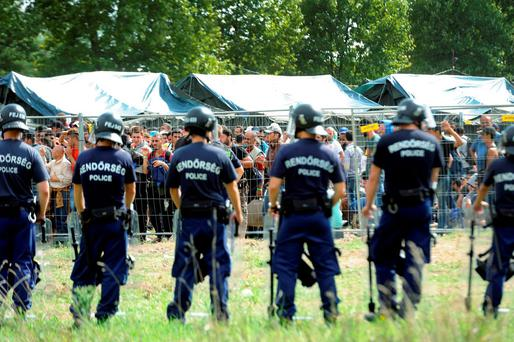 Hungarian police officers confront refugees outside the reception centre, in Roszke, southeast of Budapest, Hungary