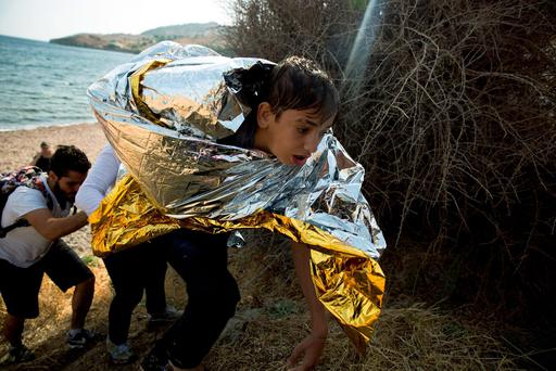 A young Syrian boy, wrapped with a thermal blanket, arrives with others after crossing aboard a dinghy from Turkey, on the island of Lesbos, Greece, Monday, Sept. 7, 2015. (AP Photo/Petros Giannakouris)