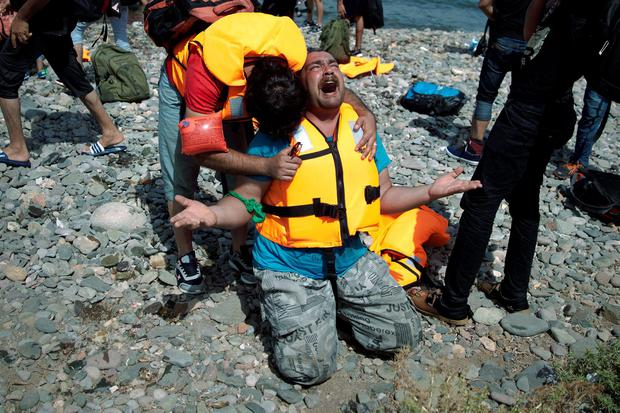 Syrian refugees react as they arrive after crossing aboard a dinghy from Turkey, on the island of Lesbos, Greece, Monday, Sept. 7, 2015. The island of some 100,000 residents has been transformed by the sudden new population of some 20,000 refugees and migrants, mostly from Syria, Iraq and Afghanistan. (AP Photo/Petros Giannakouris)