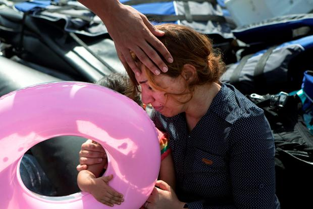 A Syrian refugee holding her child is comforted moments after arriving on a dinghy on the Greek island of Lesbos, September 7, 2015. Greece is struggling to cope with the hundreds of migrants and refugees from the war in Syria making the short crossing every day from Turkey to Greece's eastern islands, including Kos, Lesbos, Samos and Agathonisi. REUTERS/Dimitris Michalakis
