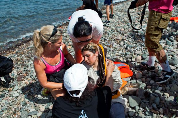 Volunteers help a Syrian refugee (C) that collapsed moments after arriving on a dinghy on the Greek island of Lesbos, September 7, 2015. Greece is struggling to cope with the hundreds of migrants and refugees from the war in Syria making the short crossing every day from Turkey to Greece's eastern islands, including Kos, Lesbos, Samos and Agathonisi. REUTERS/Dimitris Michalakis