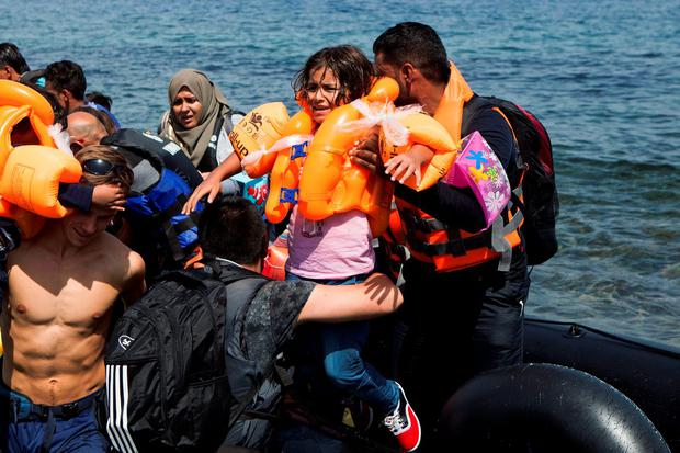 A Syrian refugee girl cries as she is aided to disembark from a dinghy, moments after arriving on a beach on the Greek island of Lesbos, September 7, 2015. REUTERS/Dimitris Michalakis