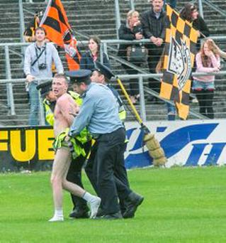 A streaker found himself being ushered off the pitch quickly by gardai at Nowlan Park during the Kilkenny homecoming. Photo: Pat Moore.