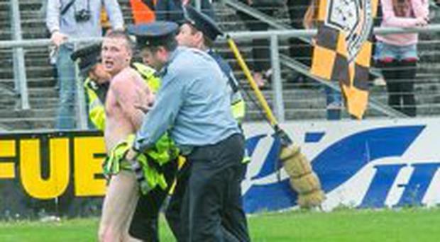 7/9/2015: A streaker found himself being ushered off the pitch quickly by gardai at Nowlan Park during the Kilkenny homecoming. Photo: Pat Moore.