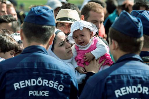 A refugee waits to board a bus in Hungary with her infant