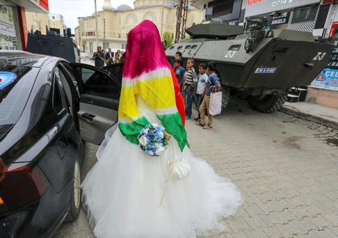 Bride Dilges Baskin, her face covered by a scarf with yellow-red-green Kurdish colours, climbs into her wedding car near armoured police vehicles (in the background) in Yuksekova, in the Kurdish-dominated southeastern Hakkari province of Turkey