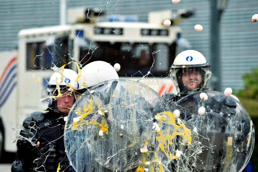 Policemen are hit by eggs as a protest by thousands of angry farmers outside an emergency meeting of farm ministers at EU headquarters in Brussels descended into confrontation. Photo: Eric Vidal (Reuters)