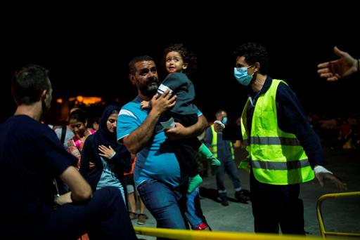 A Syrian man and his child board a ferry traveling to Athens, at the port of Lesbos Island, Greece, on Monday, Sept. 7, 2015. The island of some 100,000 residents has been transformed by the sudden new population of some 20,000 refugees and migrants, mostly from Syria, Iraq and Afghanistan. (AP Photo/Santi Palacios)