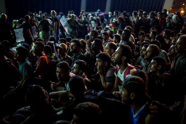 Syrian people wait at the port of Lesbos island, Greece, to board a ferry traveling to Athens, on Monday, Sept. 7, 2015. The island of some 100,000 residents has been transformed by the sudden new population of some 20,000 refugees and migrants, mostly from Syria, Iraq and Afghanistan. (AP Photo/Santi Palacios)