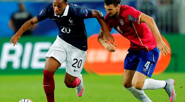 France's Anthony Martial (L) challenges Serbia's Nenad Tomovic during their friendly soccer match at Matmut Atlantique stadium in Bordeaux last night