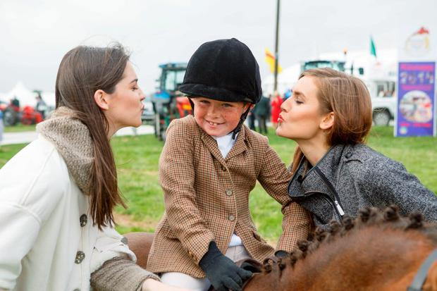 A hit with the ladies: young Niall Byrne gets a kiss from Niamh Kennedy and Sintija Zorge at the launch of the National Ploughing Championships in Co Laois. Photo: Jeff Harvey