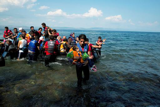 A man carries a child as refugees arrive on a dinghy after crossing from Turkey to the Greek island of Lesbos. Photo: AP