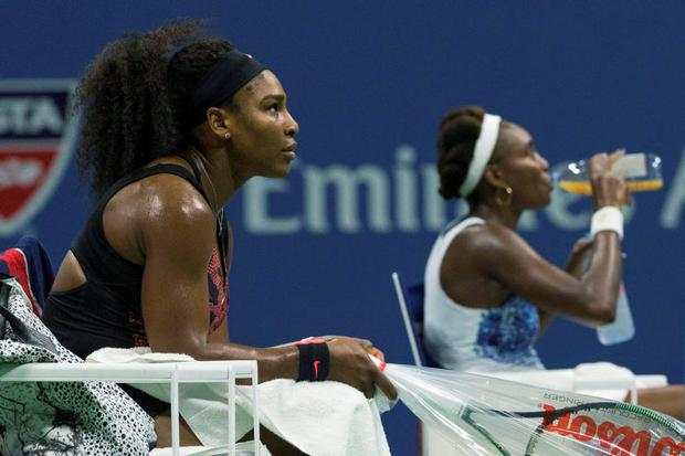 Serena Williams of the U.S. (L) and her sister Venus Williams rest between games during their quarterfinals match at the U.S. Open Championships tennis tournament in New York