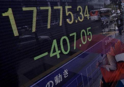 A pedestrian holding her umbrella is reflected on an electronic board showing the Japan's Nikkei average outside a brokerage in Tokyo, Japan, September 4, 2015. REUTERS/Yuya Shino