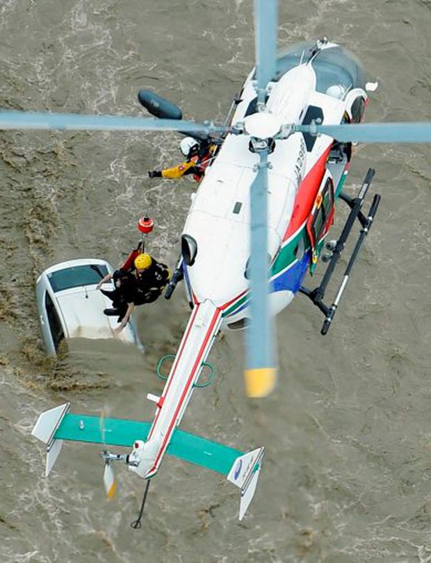 A resident is rescued by a rescue helicopter at a residential area flooded by the Kinugawa river, caused by typhoon Etau