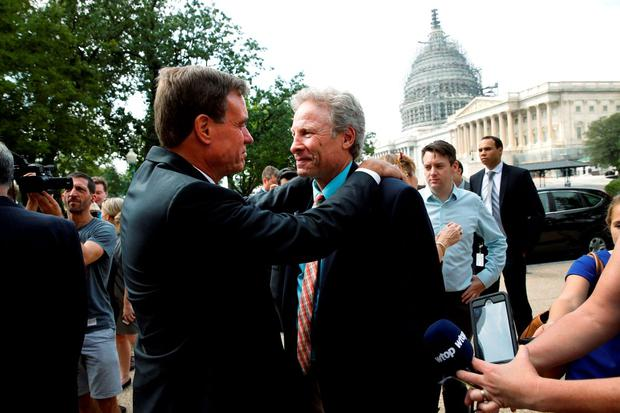 U.S. Senator Mark Warner (D-VA) (L) greets Andy Parker (C), the father of slain WDBJ reporter Alison Parker who was shot and killed on live TV in August, as they arrive to participate in a rally against gun violence, on the U.S. Capitol grounds in Washington September 10, 2015. REUTERS/Jonathan Ernst