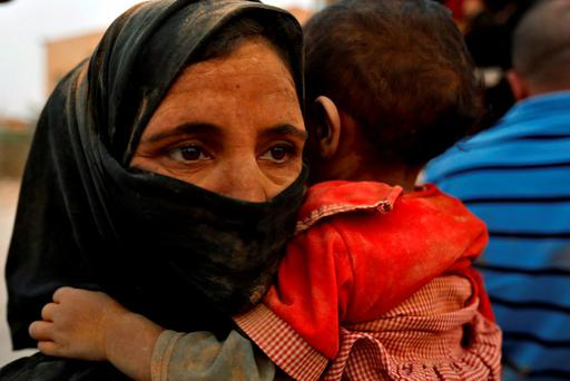 A Syrian refugee woman covered with dust carries her daughter