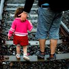A migrant helps his daughter walk on the railway track after crossing the Serbian-Hungarian border near Roszke, in southern Hungary. Photo: Matthias Schrader/AP