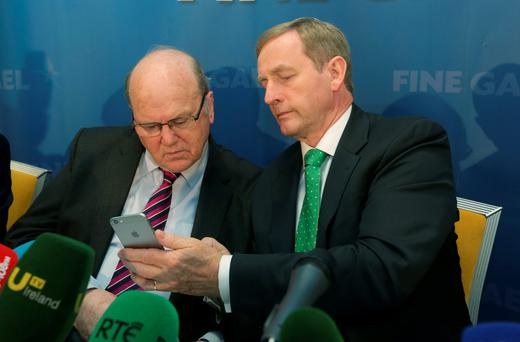 Enda Kenny shows a message on his phone to Finance Minister Michael Noonan on the last day of the Fine Gael think-in. Photo: Damien Eagers