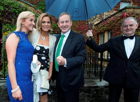 Ciara Brady and Alma Brophy, both from Carlow, brave the elements yesterday to meet Taoiseach Enda Kenny as he leaves Fine Gael's two-day think-in in Adare, Co Limerick, yesterday