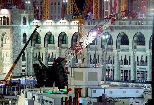 A towering construction crane, center, is seen collapsed over the Grand Mosque, in Mecca, Saudi Arabia, early Saturday morning, Sept. 12, 2015. The towering construction crane toppled over on Friday during a violent rainstorm in the Saudi city of Mecca, Islam's holiest site, crashing into the Grand Mosque, ahead of the start of the annual hajj pilgrimage later this month.(AP Photo)