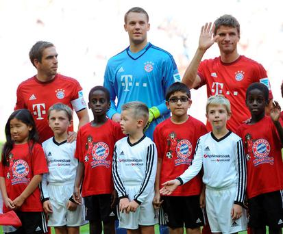 Back row from left: Munich players Philipp Lahm, goal keeper Manuel Neuer and Thomas Mueller pose with migrant and refugee children before the German Bundesliga soccer match between FC Bayern Munich and FC Augsburg at the Allianz Arena in Munich, Germany