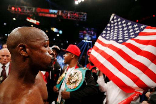 Floyd Mayweather Jr., left, reacts toward fans before his welterweight title boxing bout against Andre Berto on Saturday
