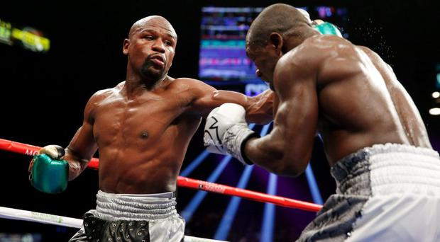 Floyd Mayweather Jr. hits Andre Berto during their welterweight title boxing bout Saturday, Sept. 12, 2015, in Las Vegas. (AP Photo/John Locher)