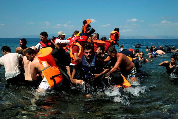 Syrian and Afghan refugees are helped by locals as they reach the shore after their dinghy deflated Credit: Alkis Konstantinidis (Reuters)