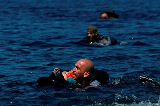 A Syrian refugee holding a baby in a lifetube as he swims towards the shore after their dinghy deflated some 100m away from the Greek island of Lesbos Credit: Alkis Konstantinidis (Reuters)