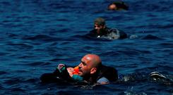 A Syrian refugee holding a baby in a lifetube swims towards the shore after their dinghy deflated some 100m away before reaching the Greek island of Lesbos, September 13, 2015. REUTERS/Alkis Konstantinidis