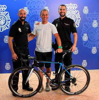 Spanish police alongside a member of team Orica Greenedge with the recovered bike Credit: Malaga Police