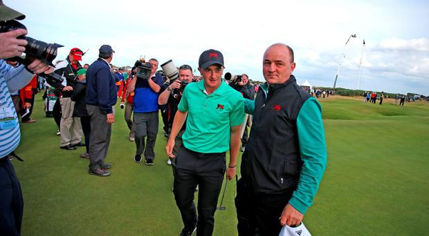 Great Britain and Ireland captain Nigel Edwards and Paul Dunne walk off 18th green after he secured the victory over the USAputts on the first green during day two of the Walker Cup at Royal Lytham & St Annes Golf Club