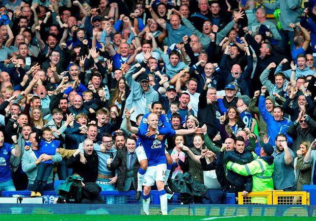 Everton's English midfielder Aaron Lennon (R) celebrates with Everton's Scottish striker Steven Naismith after Naismith scored his third goal