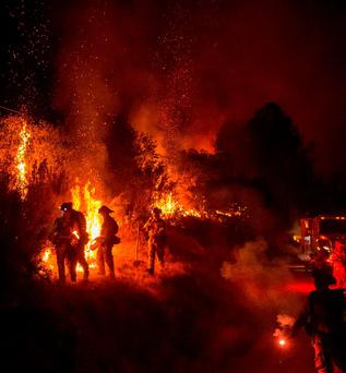 Firefighters light backfires while battling the Butte fire near San Andreas, California