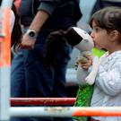 A refugee girl kisses her doll after arriving in Munich station