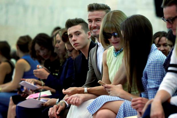 David Beckham, center, husband of designer Victoria Beckham, and their son Brooklyn Beckham, sit in the front row as they wait for her Spring 2016 collection to be modeled during Fashion Week, in New York, Sunday, Sept. 13, 2015. Seated second from right is Anna Wintour, editor-in-chief of American Vogue. (AP Photo/Richard Drew)