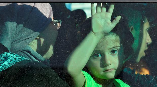 A Syrian refugee girl looks out the window from inside a bus after disembarking a passenger ship at the port of Piraeus, near Athens, Greece. Photo: REUTERS/Michalis Karagiannis