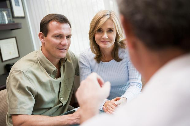 Couple in consultation at IVF clinic talking to doctor. Picture posed