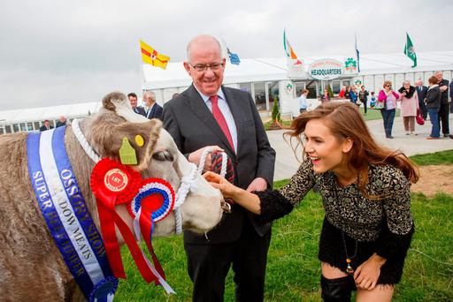 How do you moo? Minister for Foreign Affairs Charlie Flanagan TD with Sintija Zorge and First Prize Belgian Blue Heifer at Tullamore Show at the official launch of the National Ploughing Championships at Ratheniska, Co. Laois. Picture: Jeff Harvey