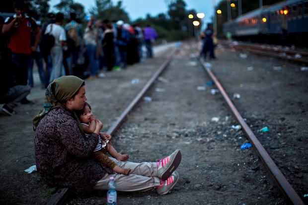 An Afghan refugee woman holding her daughter rests while waiting to board a train heading to the Austrian border. It is obvious that what we are now witnessing a disaster of global proportions that demands a global solution.