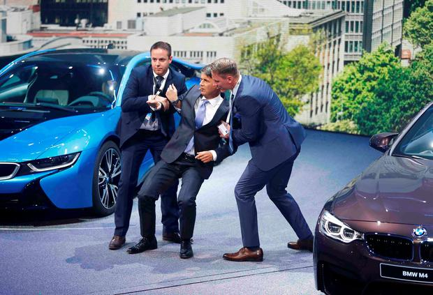 BMW CEO Harald Krueger (C) is helped after he collapsed at a presentation during the media day at the Frankfurt Motor Show (IAA) in Frankfurt, Germany, September 15, 2015. REUTERS/Kai Pfaffenbach