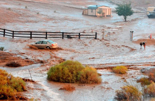 A vehicle crosses a flooded section of Carob Street, Tuesday, Sept. 8, 2015, in Hesperia, Calif. The National Weather Service issued a flash flood warning and severe thunderstorm warning for the area on Tuesday night. (David Pardo/The Victor Valley Daily Press via AP)