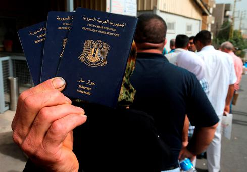A Syrian man holds his family's passports as he lines up with other to apply for asylum in Germany Credit: Hussein Malla