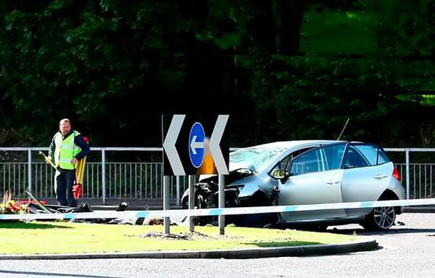 Police officers at the scene of a single-vehicle crash just off the junction of the Stewartstown road in Belfast. Picture - Kevin Scott / Presseye