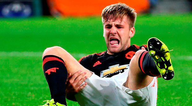 Manchester Uniteds Luke Shaw grimaces after being injured during the Champions League Group B soccer match between PSV and Manchester United at Philips stadium in Eindhoven, Netherlands