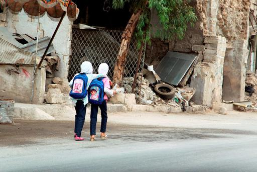 Girls walk to school in Old Aleppo, Syria, yesterday, where seven died in a suicide bomb attack. Photo: Reuters/Abdalrhman Ismail