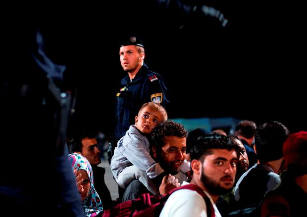 Refugees queue up for a bus, as they arrive at the border between Austria and Hungary, Heiligenkreuz, Austria, late Tuesday Sept. 15, 2015. (AP Photo/Christian Bruna)