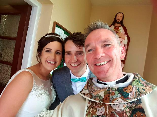 Fr John Kenny with a newly wed couple Pic: Fr John Kenny/Facebook