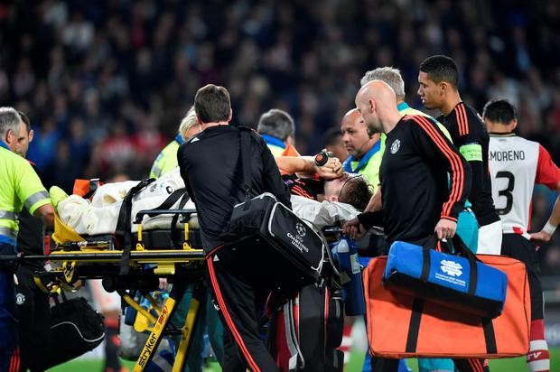 Manchester's Luke Shaw leaves the field after being injured during the UEFA Champions League Group B football match between PSV Eindhoven and Manchester United
